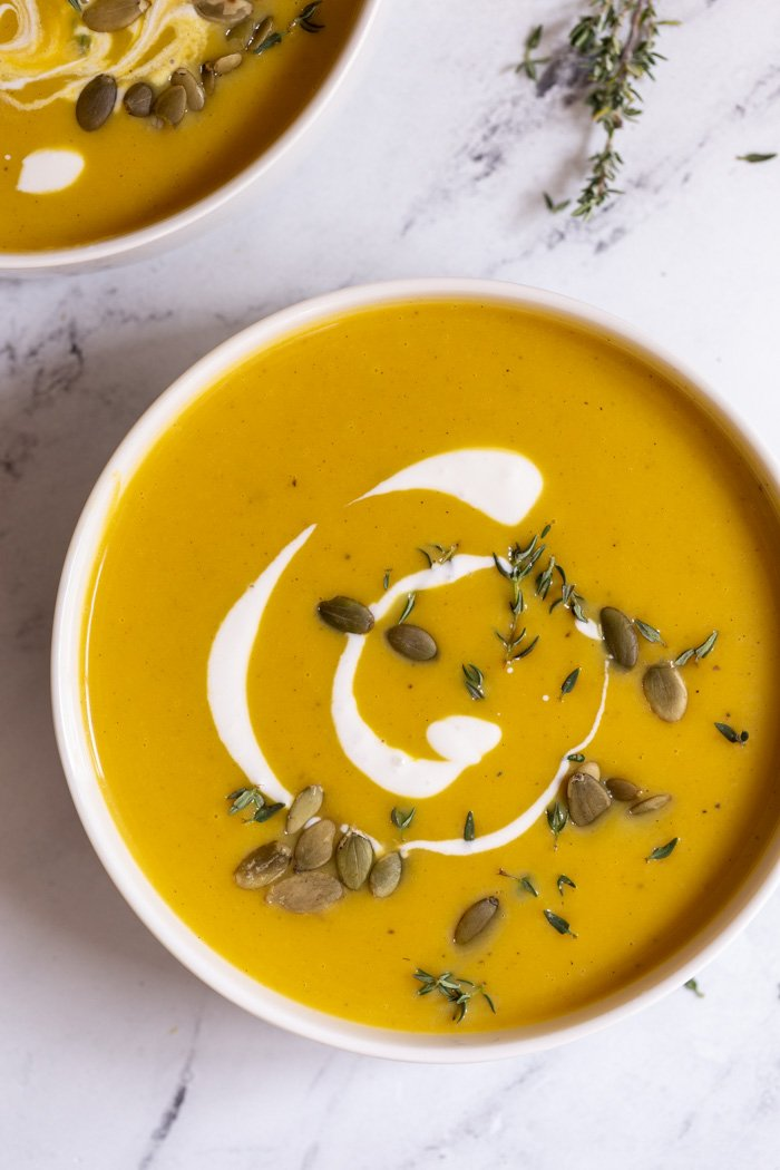 bowls filled with creamy butternut squash soup and topped with cream and pepitas