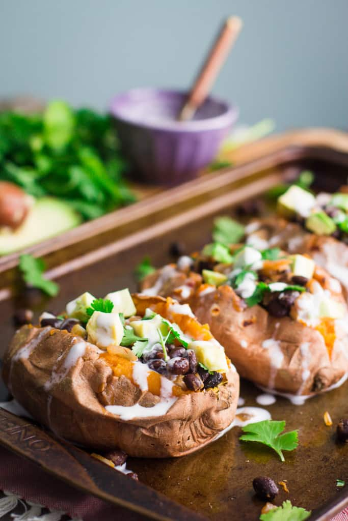 sweet potatoes stuffed with black beans and avocado on a baking tray