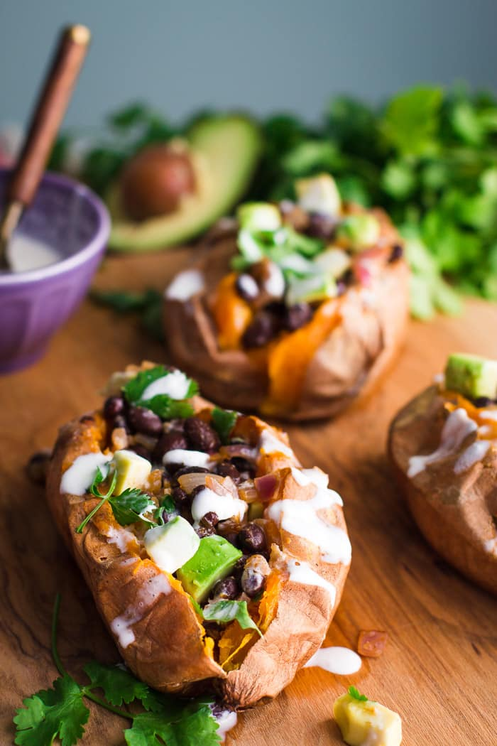 sweet potato stuffed with black beans and avocado on a wood board