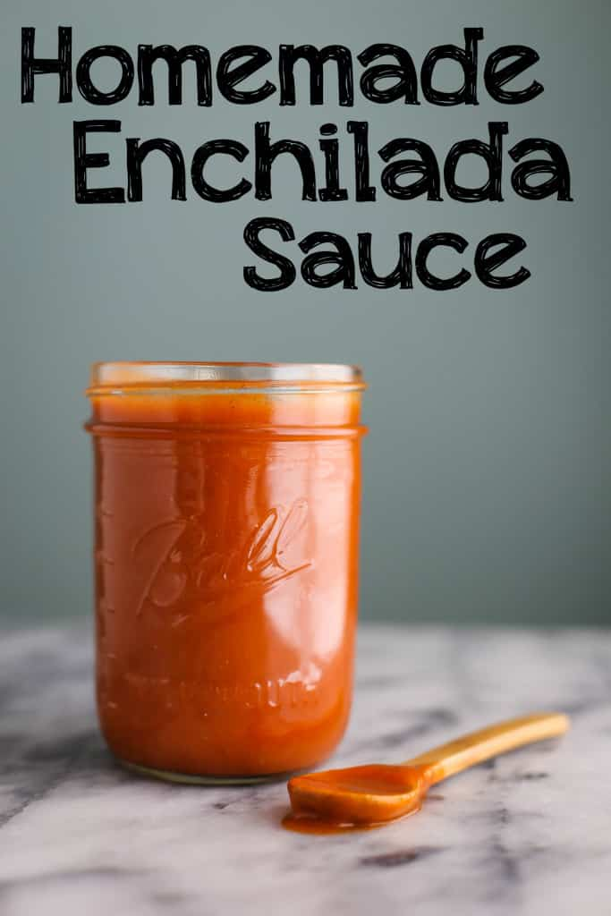 "mason jar filled with enchilada sauce. wooden spoon sitting next to the jar with a green background. textoverlay on the image that says ""homemade enchilada sauce"""