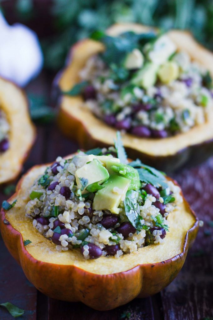 acorn squash cut in half and stuffed with quinoa nad black beans. topped with avocado and herbs