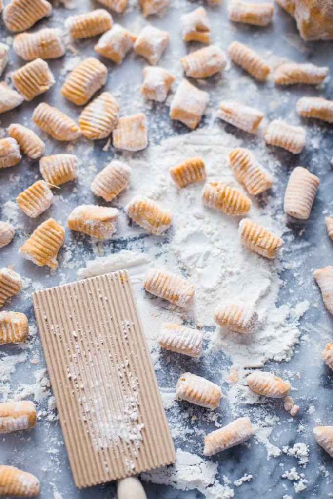 sweet potato gnocchi on a marble board with flour all around