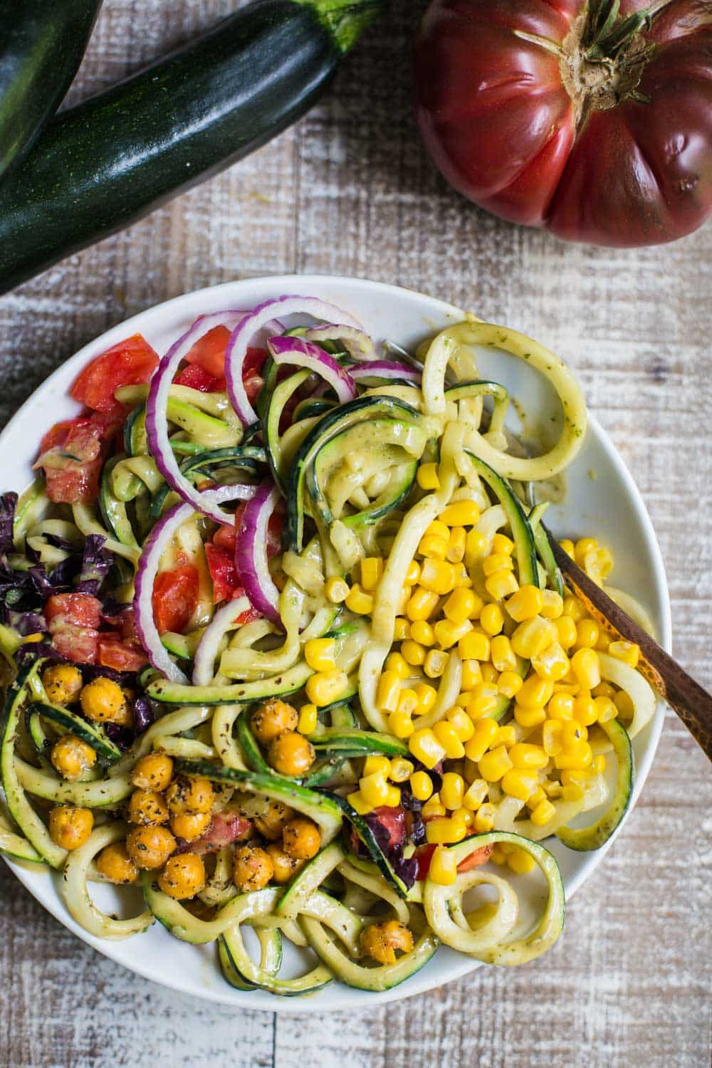 Summer Harvest Zoodles- Zucchini noodles covered in avocado sauce and topped with lots of veggies and chickpeas!!