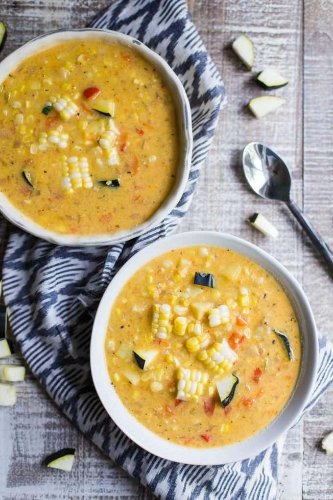 top down shot of 2 bowls of corn chowder that are both topped with fresh corn and zucchini