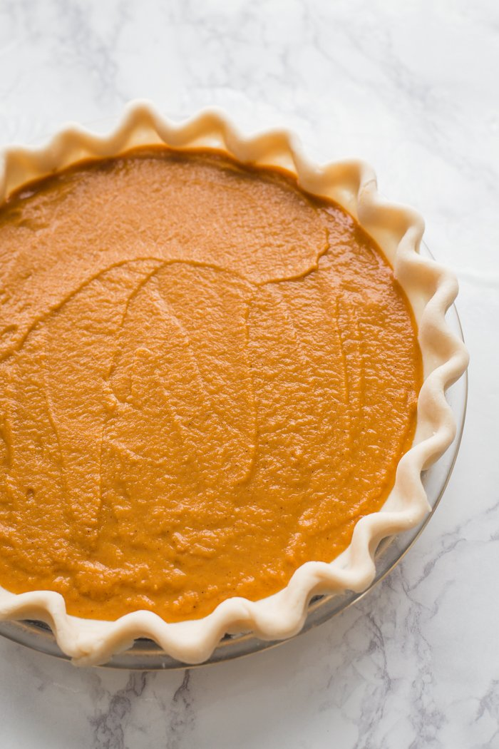 unbaked vegan pumpkin pie on a marble board