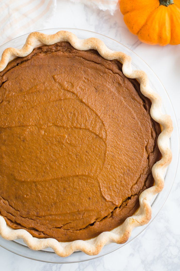 large baked pumpkin pie on a marble board with a pumpkin in the corner