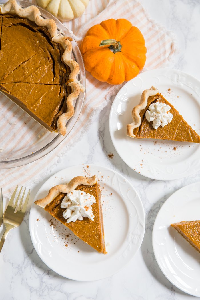 top down shot of vegan pumpkin pie slices on white plates and the full pie in the corner with a fresh pumpkin next to it