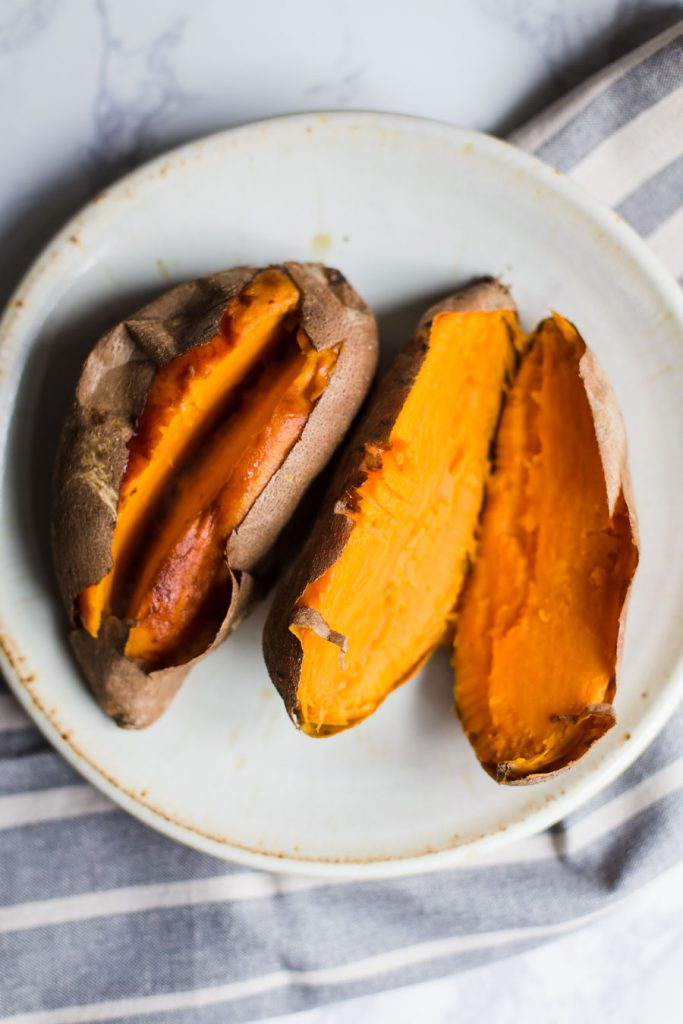 2 baked sweet potatoes cut open on a plate
