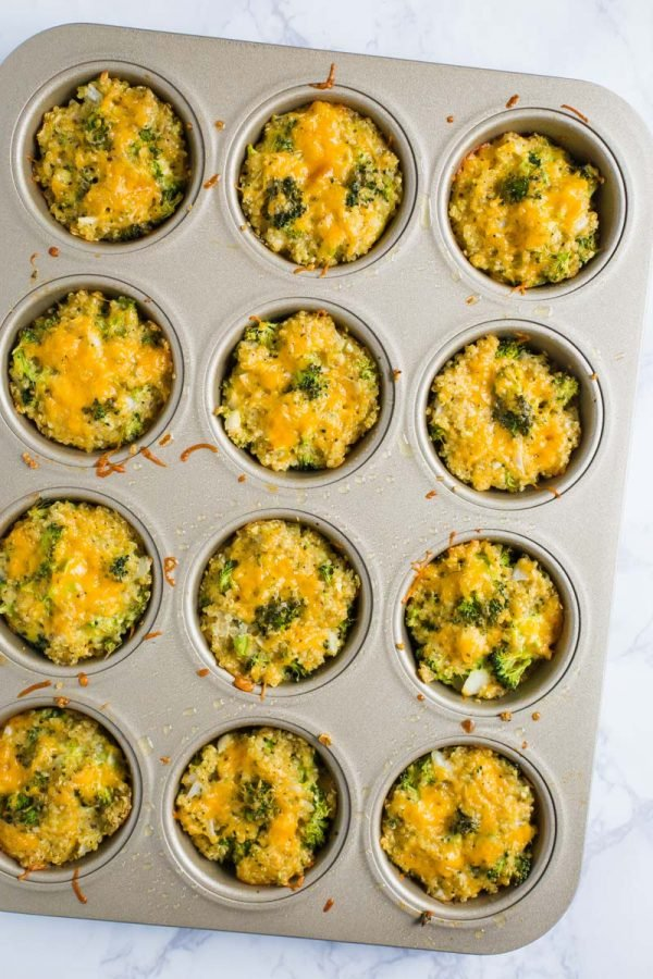 quinoa, cheddar cheese, and broccoli bites in a muffin tin on a marble board