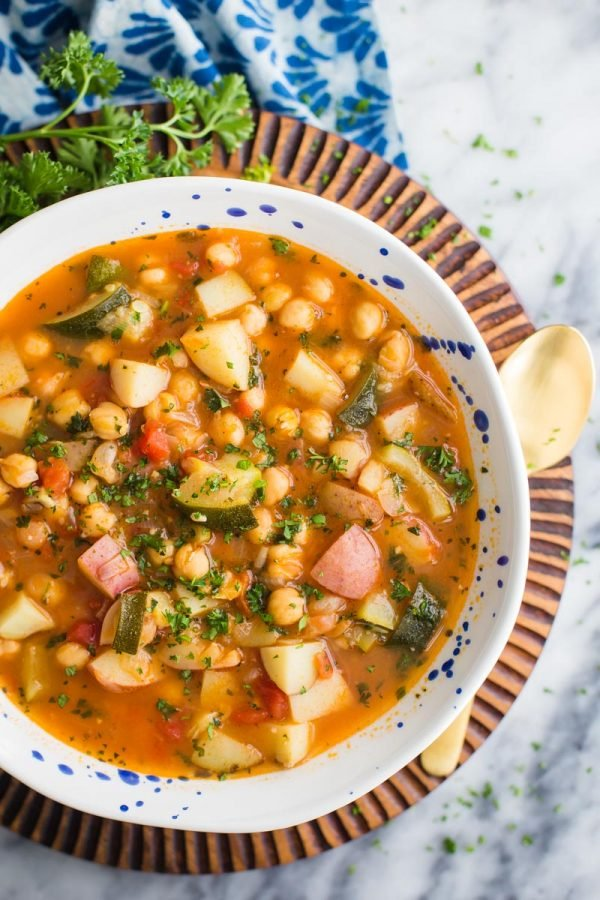 Soup with potatoes and chickpeas and other veggie on a wooden board sitting on top of a marble background.