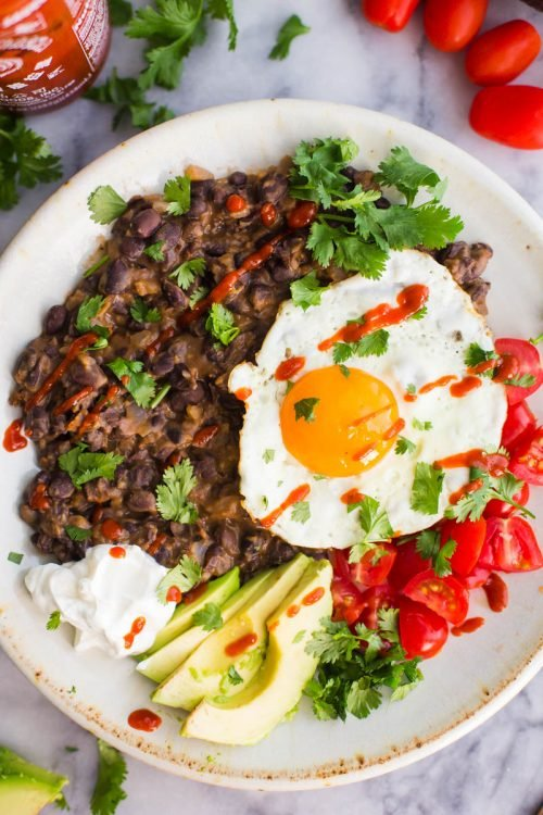 mashed blck beans on a plate with a fried egg and veggies