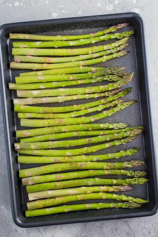 top down shot of raw asparagus spears on a dark baking sheet