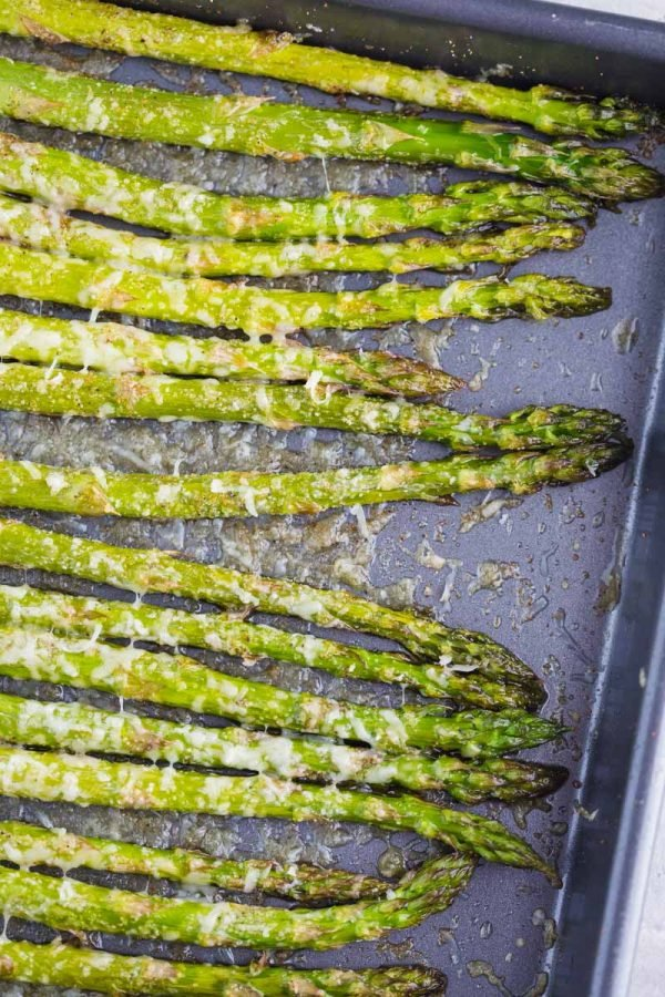Up close shot of baked asparagus on a baking sheet with melted parmesan cheese on top