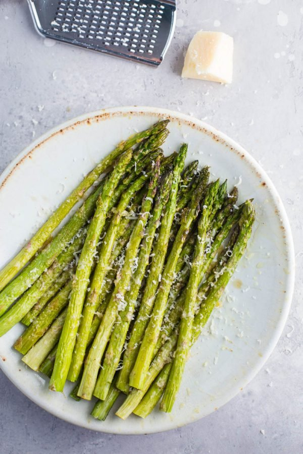 Plate full of cooked asparagus with parmesan cheese sprinkled on top and a cheese grate and cheese at the top of the photo