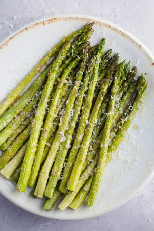 Plate full of cooked asparagus with parmesan cheese sprinkled on top