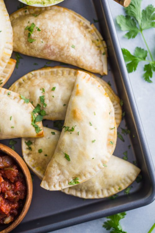 empanadas stacked up on a back tray with salsa in the corner