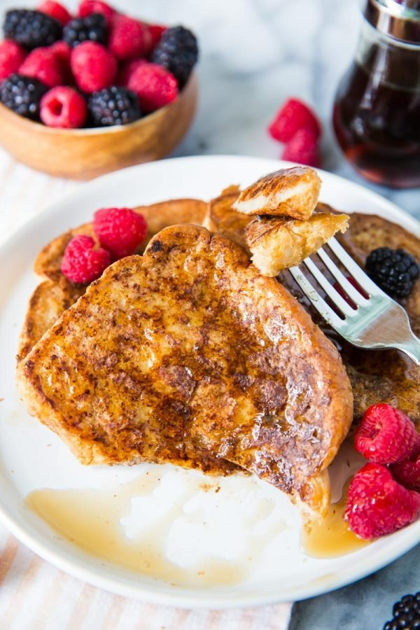 several slices of vegan french toast on a white plate topped with syrup, raspberries and blackberries. a bite has been taken out of on the the pieces