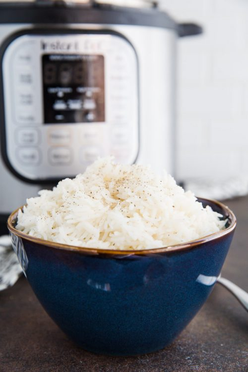 white rice in a bowl in front of a pressure cooker