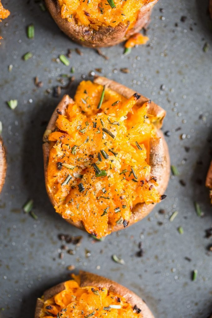 smashed sweet potato round on a baking sheet topped with pepper