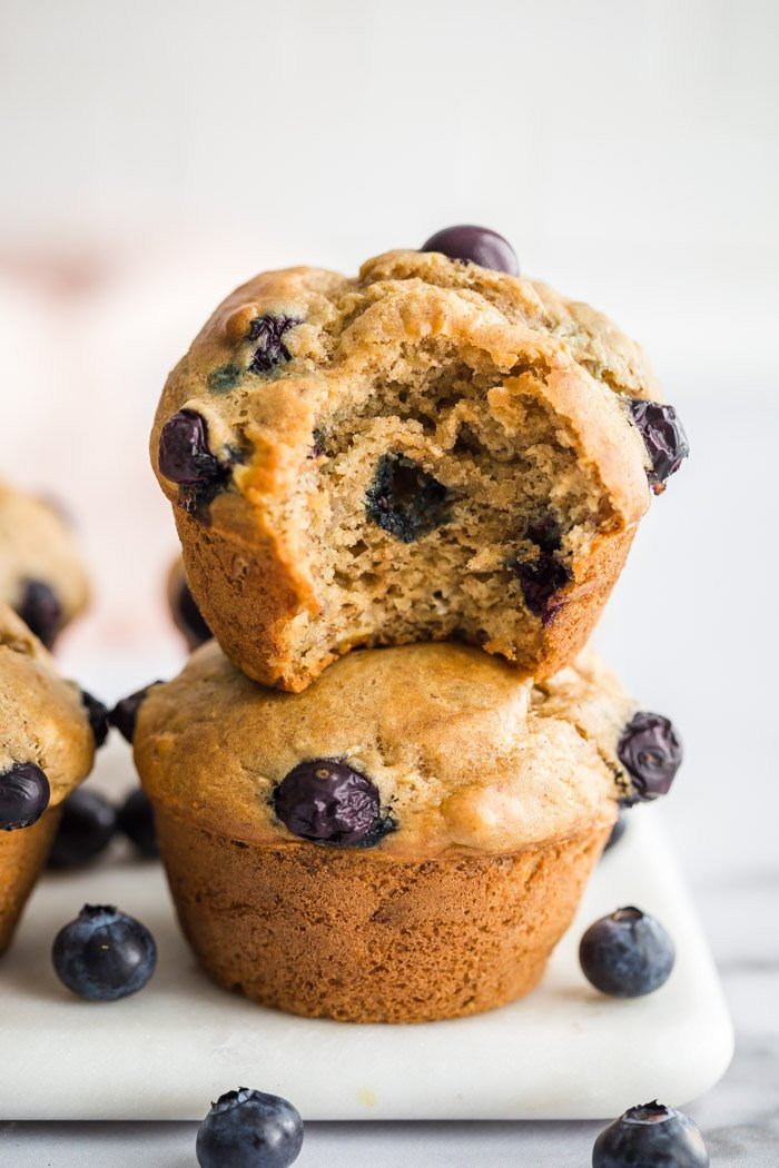 blueberry muffins stacked up on a marble board