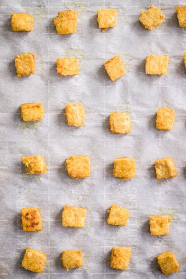 top down shot of crispy cubes of tofu lined up on a baking sheet that's lined with parchment paper