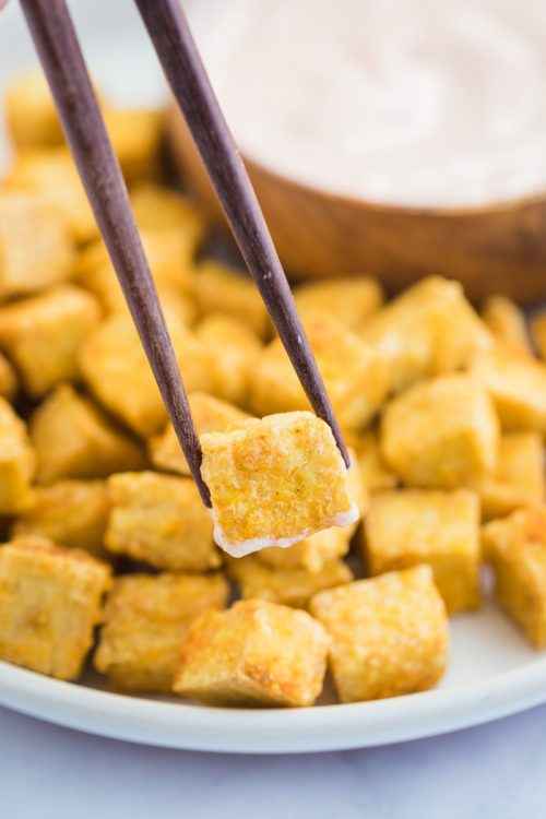 cispy tofu cube held up by chopsticks