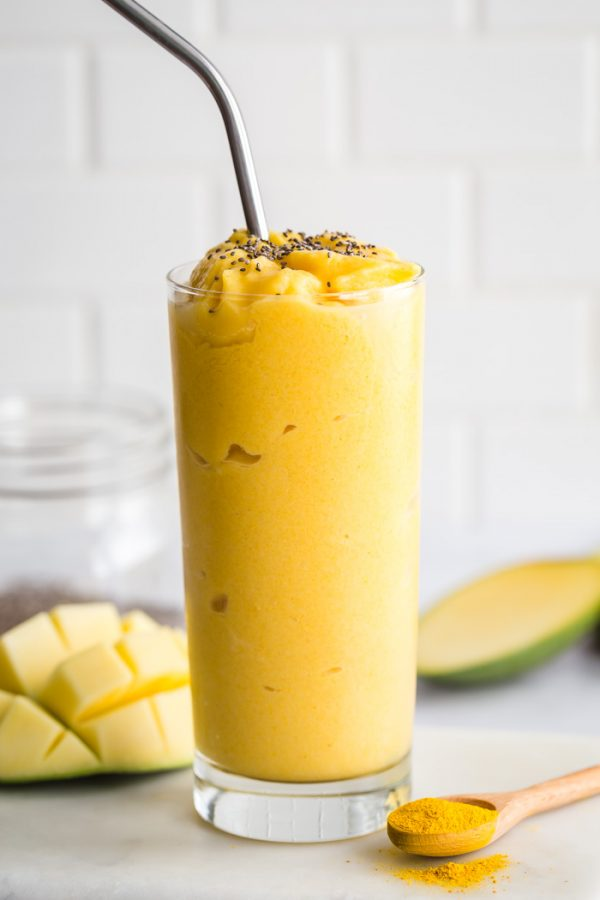 Mango smoothie with turmeric in a tall glass. mango in the background with a spoonful of turmeric to the side