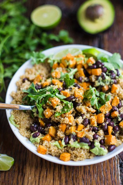 white bowl on a wood table filled with quinoa, sweet potato, and black beans mixd up