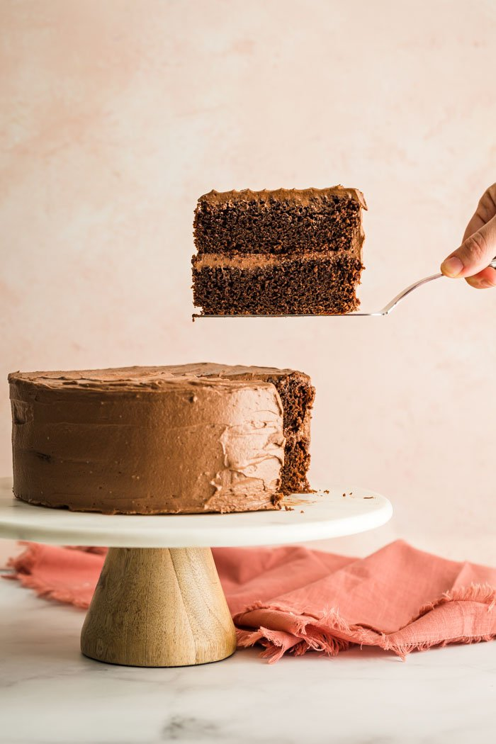 slice of chocolate cake on a marble cake stand