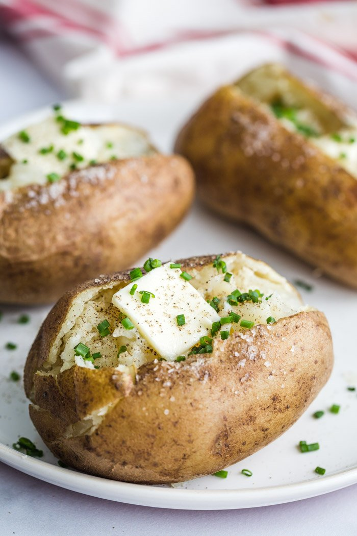 baked potatoes topped with butter and herbs