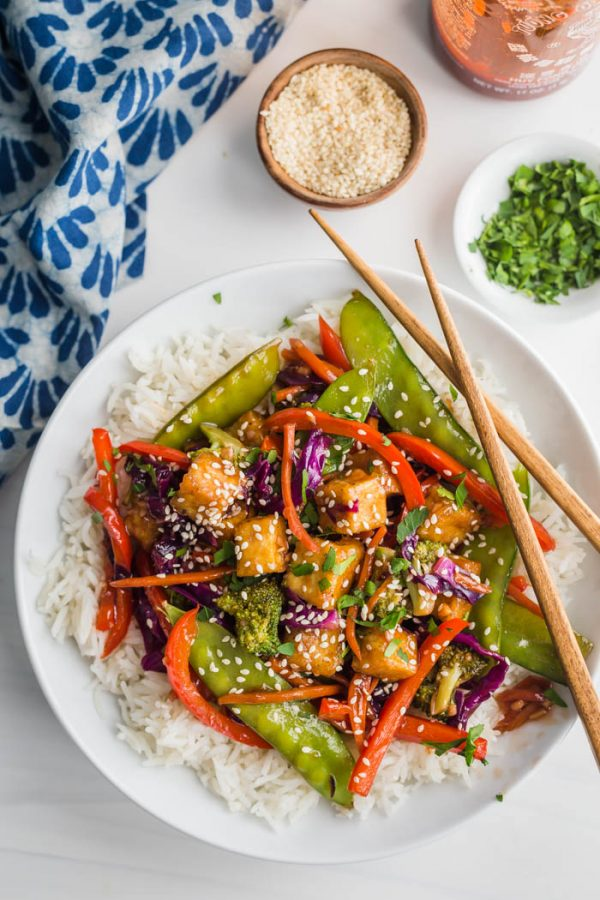 tofu stir fry served over rice on a white background