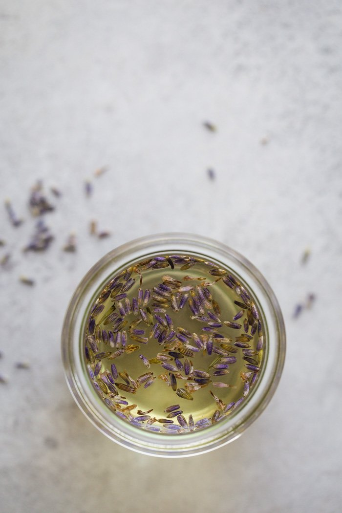 lavender simple syrup in a small glass jar. fresh lavender in it