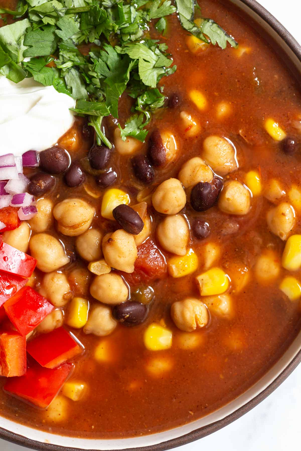 up close shot of chickpea taco soup with black beans and fresh veggies + sour cream and cilantro on top