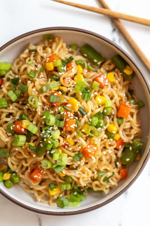 ramen noodles mixed with veggies in a bowl and topped with green onion