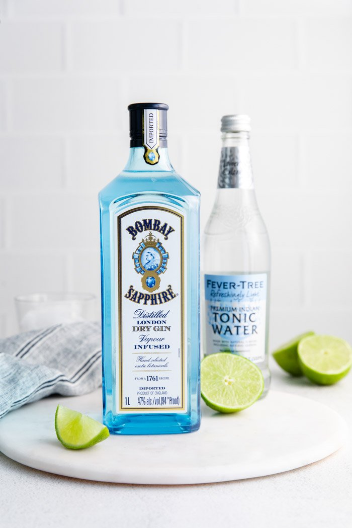 bombay saffire with limes around it and a bottle of fever hill tonic water in the background. ingredients for gin and tonic
