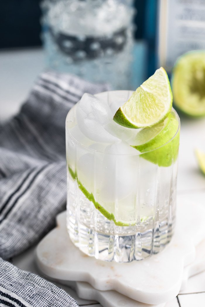 clear beveled glass filled with clear liquid (gin and tonic) plus fresh lime wedges towel on the side