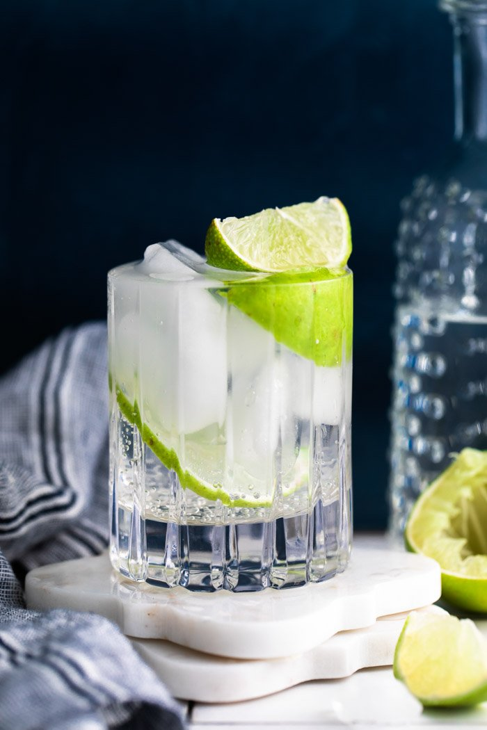 clear beveled glass filled with clear liquid (gin and tonic) plus fresh lime wedges. dark background