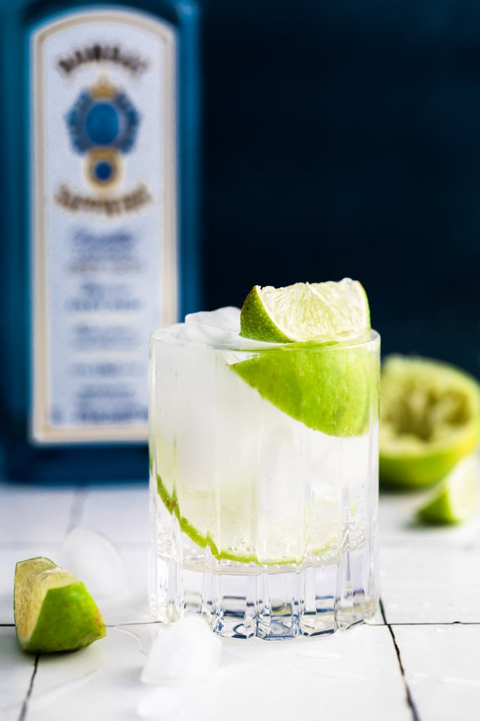 clear beveled glass filled with clear liquid (gin and tonic) plus fresh lime wedges. bombay sapphire in the background