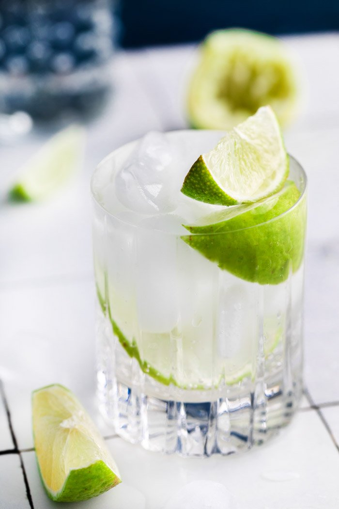 clear beveled glass filled with clear liquid (gin and tonic) plus fresh lime wedges