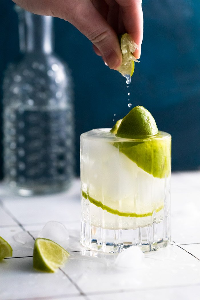 clear beveled glass filled with clear liquid (gin and tonic) plus fresh lime wedges. hand squeezing a lime wedge into the glass