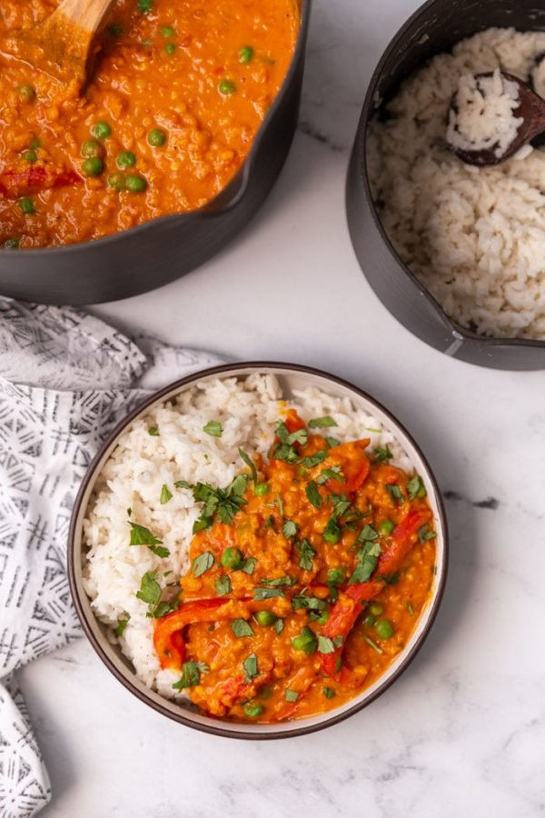 lentil curry served over white rice in a bowl with a large pot of curry and coconut rice in small pot