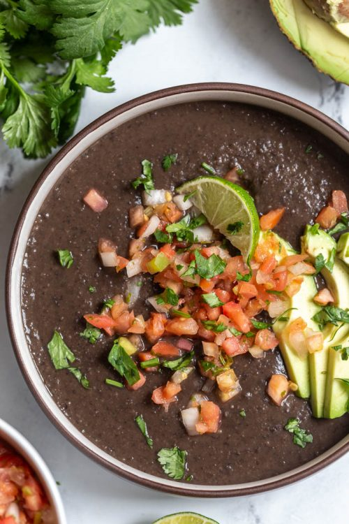 creamy black bean soup in a bowl and topped with pico de gallo, avocado, and lime
