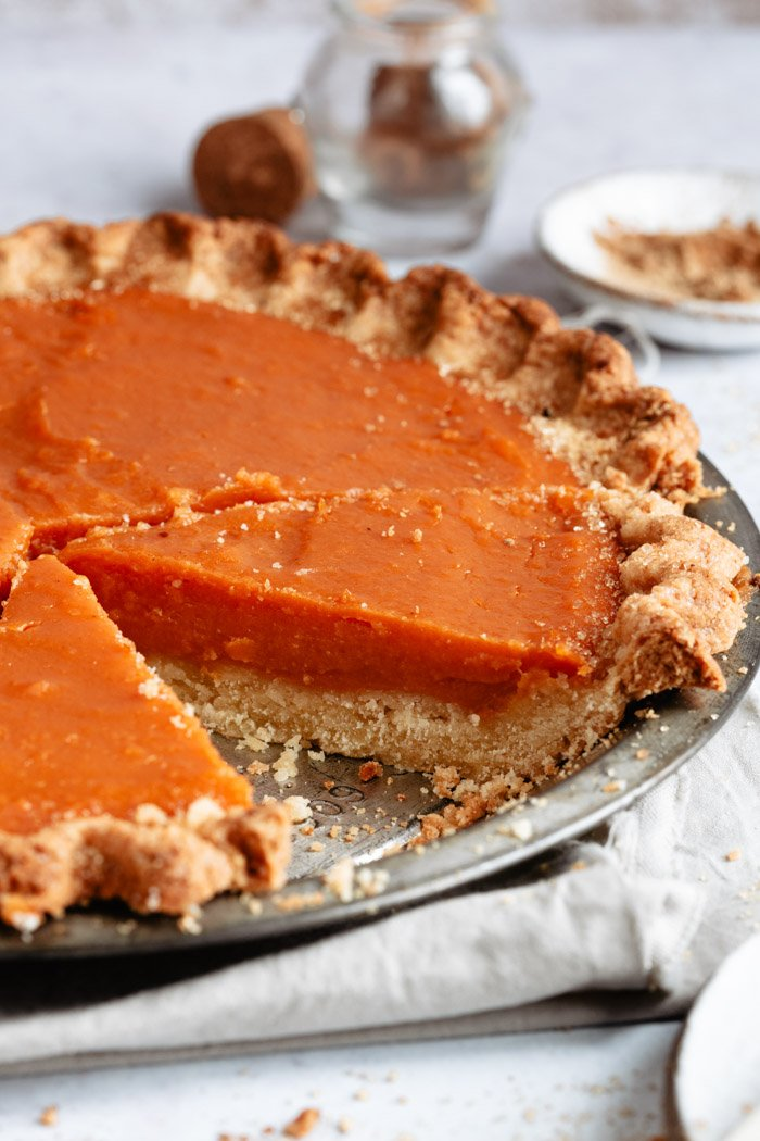 side shot of a sweet potato pie with a slice taken out
