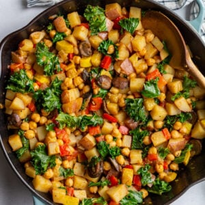 stirring vegan hash with a wooden spoon in a large skillet