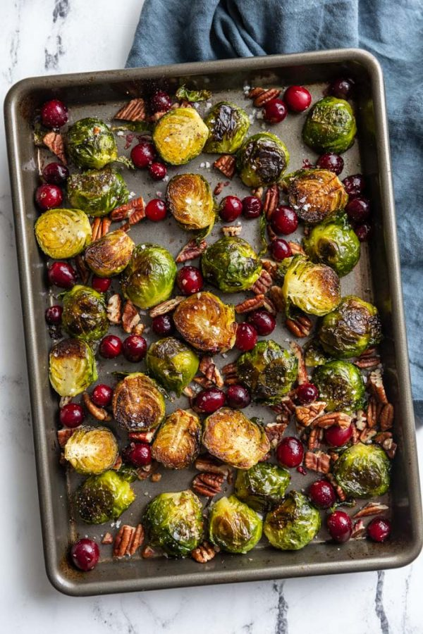 roasted brussels sprouts and cranberries on a baking tray