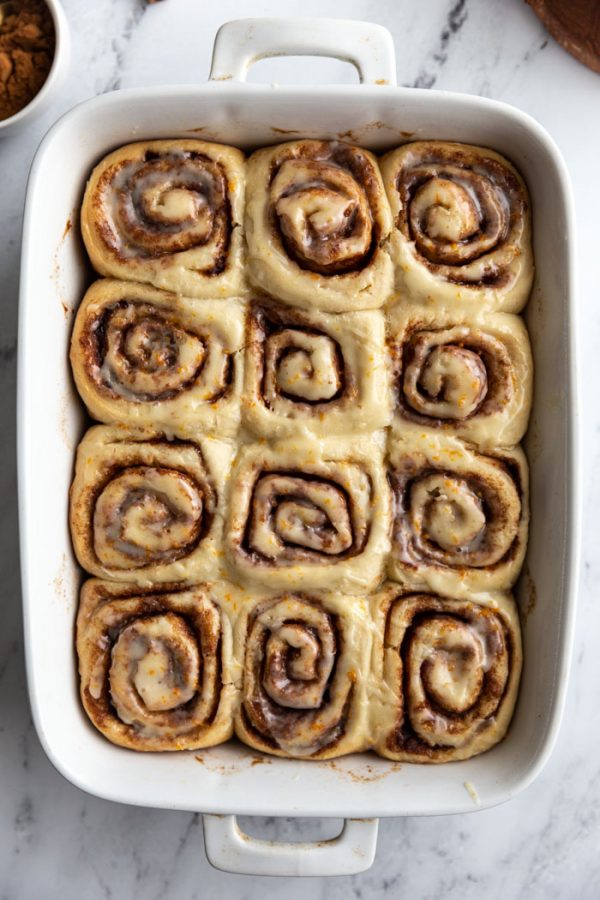vegan cinnamon rolls iced in a baking tray
