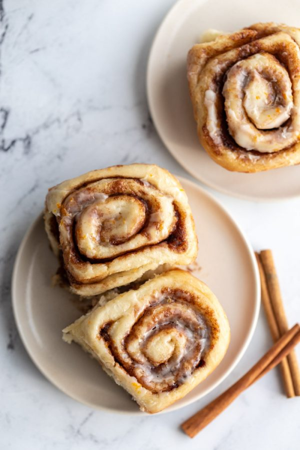 cinnamon rolls on a plate with cinnamon sticks nearby
