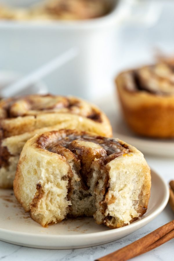 cinnamon roll on a plate with a bite taken out
