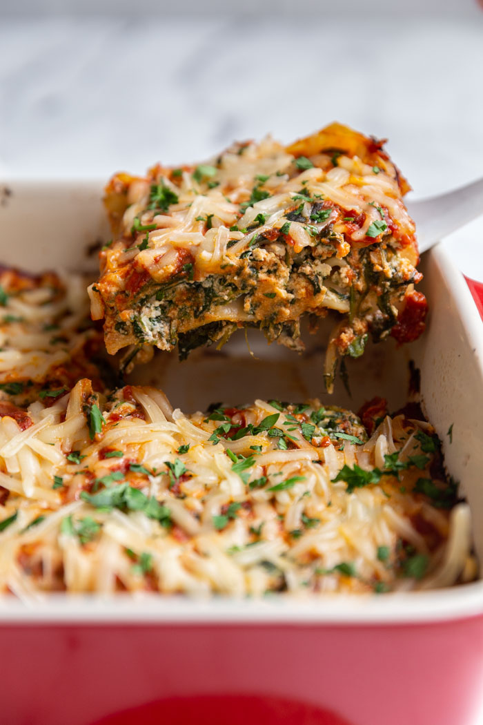 scoopful of lasagna being pulled out of a casserole dish