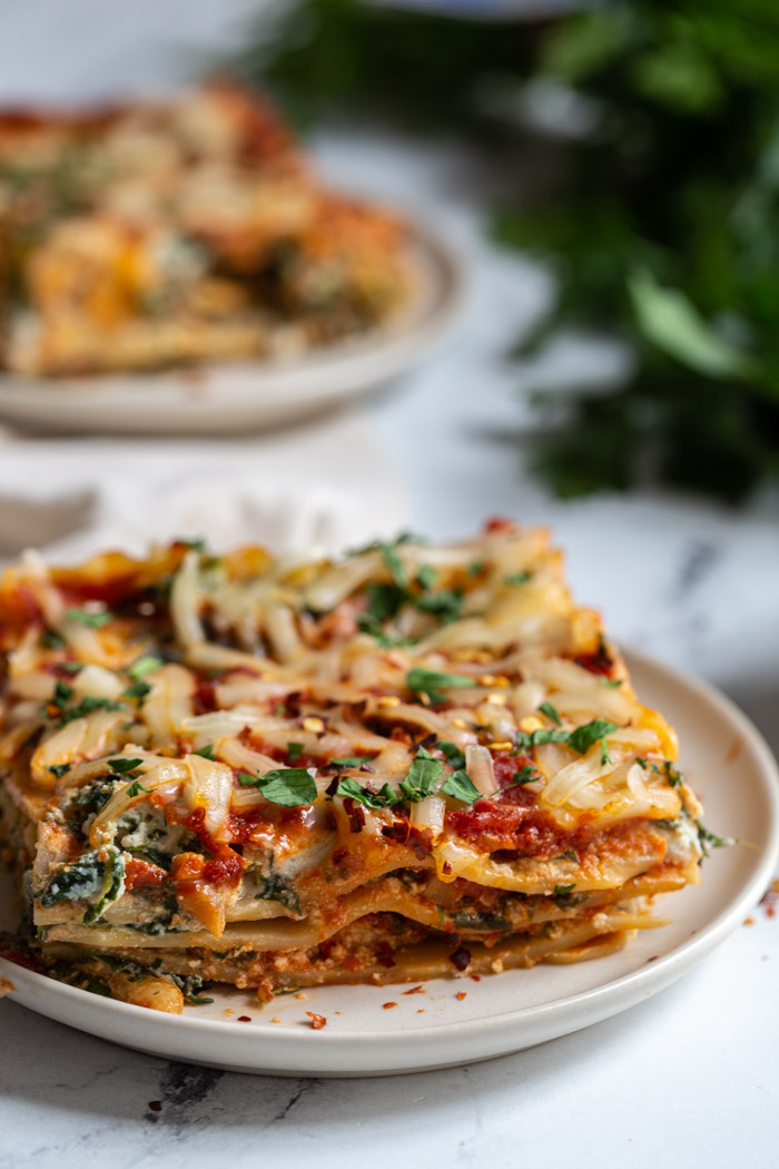 2 plates of vegan lasagna with parsley in the back